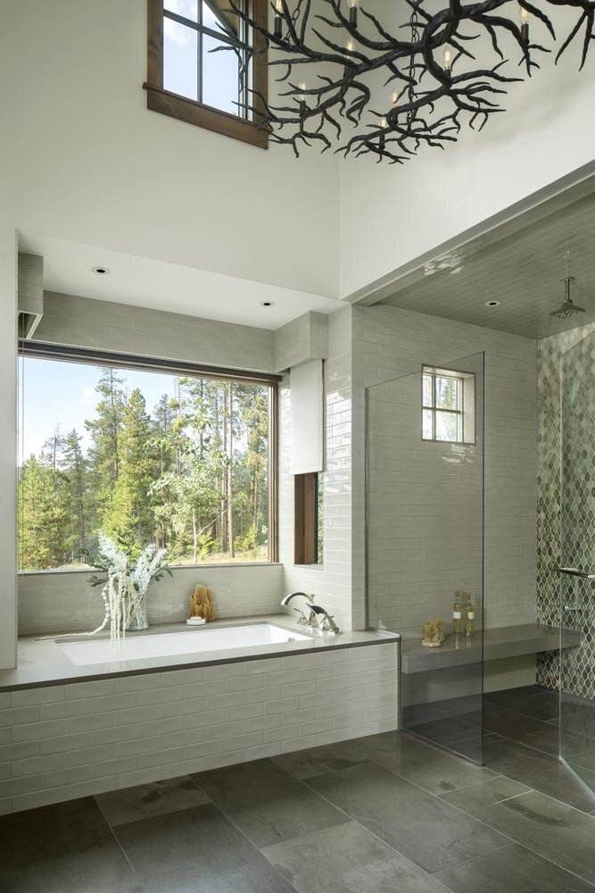 Bath Room, Granite Counter, Soaking Tub, Mosaic Tile Wall, Concrete Floor, Accent Lighting, Ceramic Tile Floor, Travertine Floor, Slate Floor, Stone Counter, Full Shower, Ceiling Lighting, Drop In Tub, Stone Tile Wall, Enclosed Shower, Porcelain Tile Wall, Quartzite Counter, Corner Shower, Alcove Tub, and Ceramic Tile Wall The spa-like handmade ceramic shower tile gleams in the master bathroom where a metal branch-like chandelier adds a touch of nature.  Fairways at Pole Creek