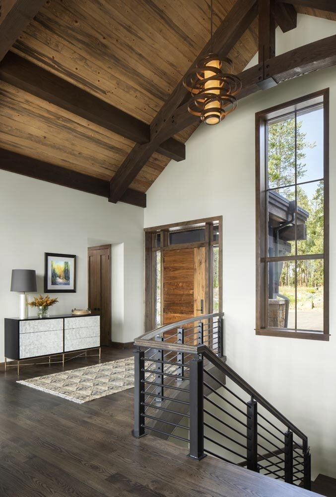 Hallway and Dark Hardwood Floor The smooth raw steel complements the textured exposed stone wall, oak floors and beetle kill pine ceiling—a rustic and contemporary mix found throughout the interior.  Fairways at Pole Creek
