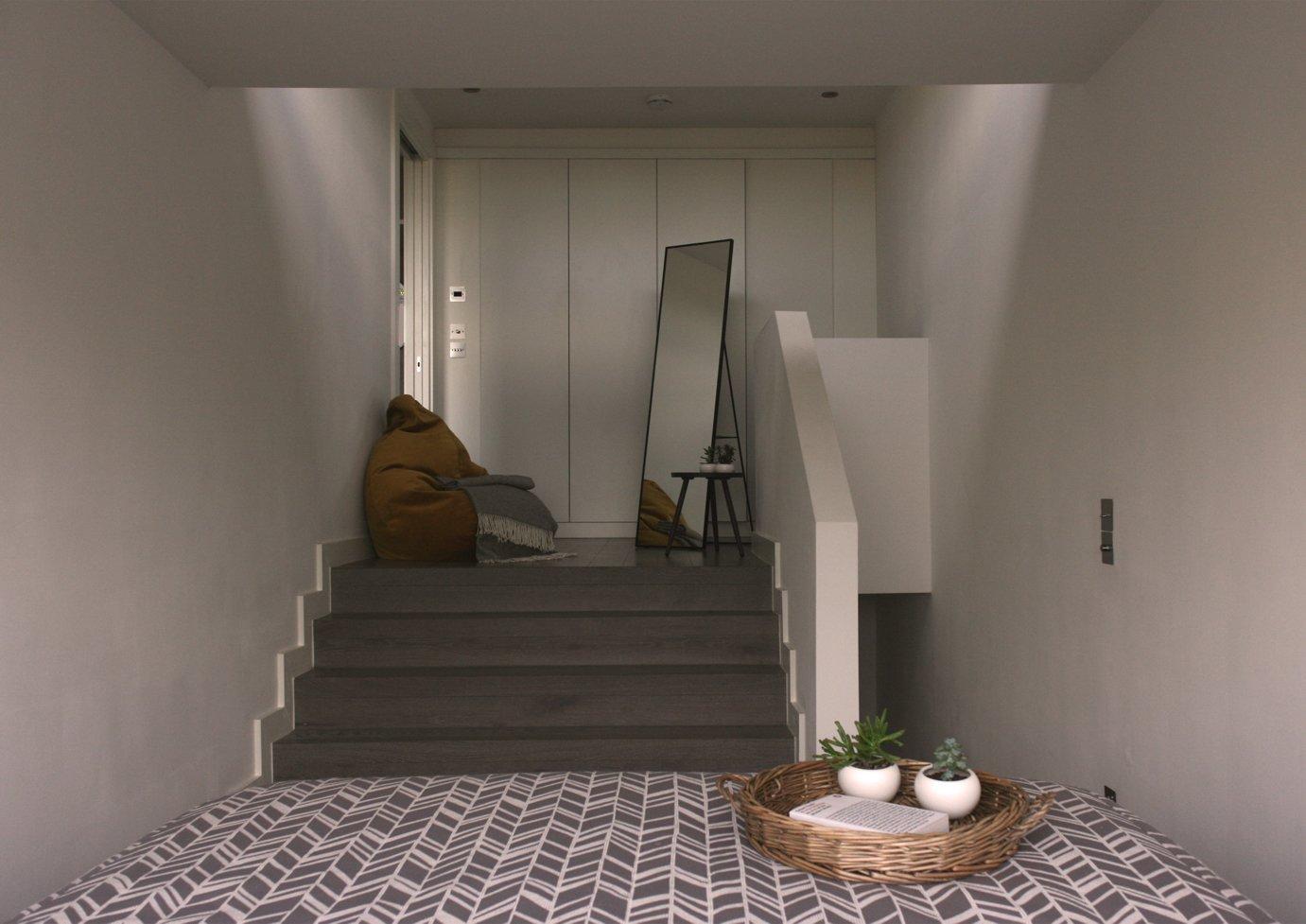 Bedroom, Light Hardwood Floor, and Chair Master bedroom with lounge area  The Yellow Door by Tactus Design Workshop