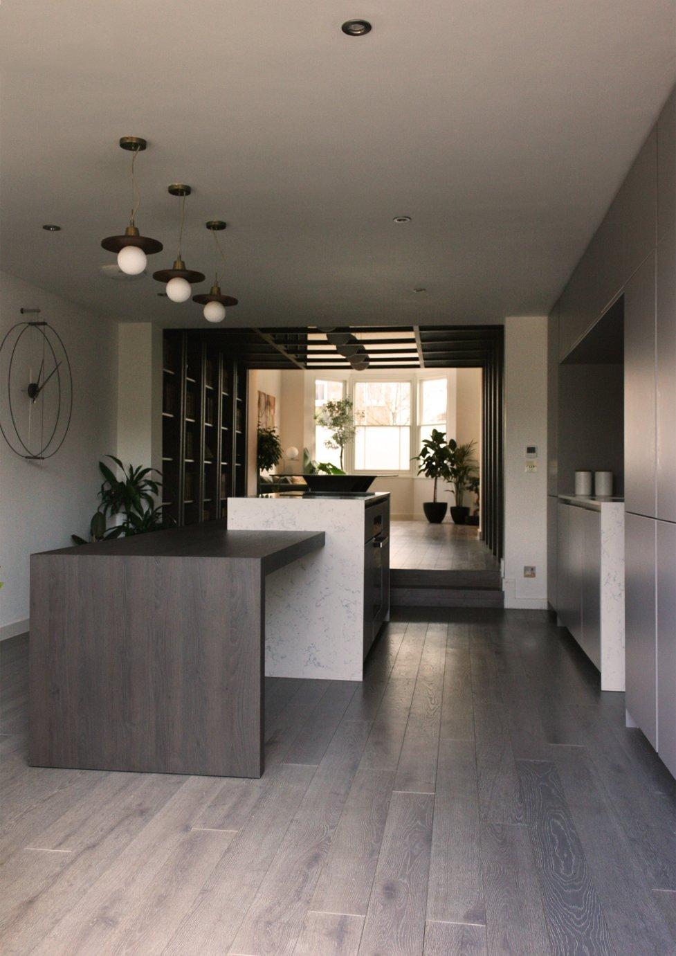Kitchen, Engineered Quartz Counter, Open Cabinet, Light Hardwood Floor, Subway Tile Backsplashe, and Pendant Lighting Kitchen with bespoke integrated informal dining table  The Yellow Door by Tactus Design Workshop