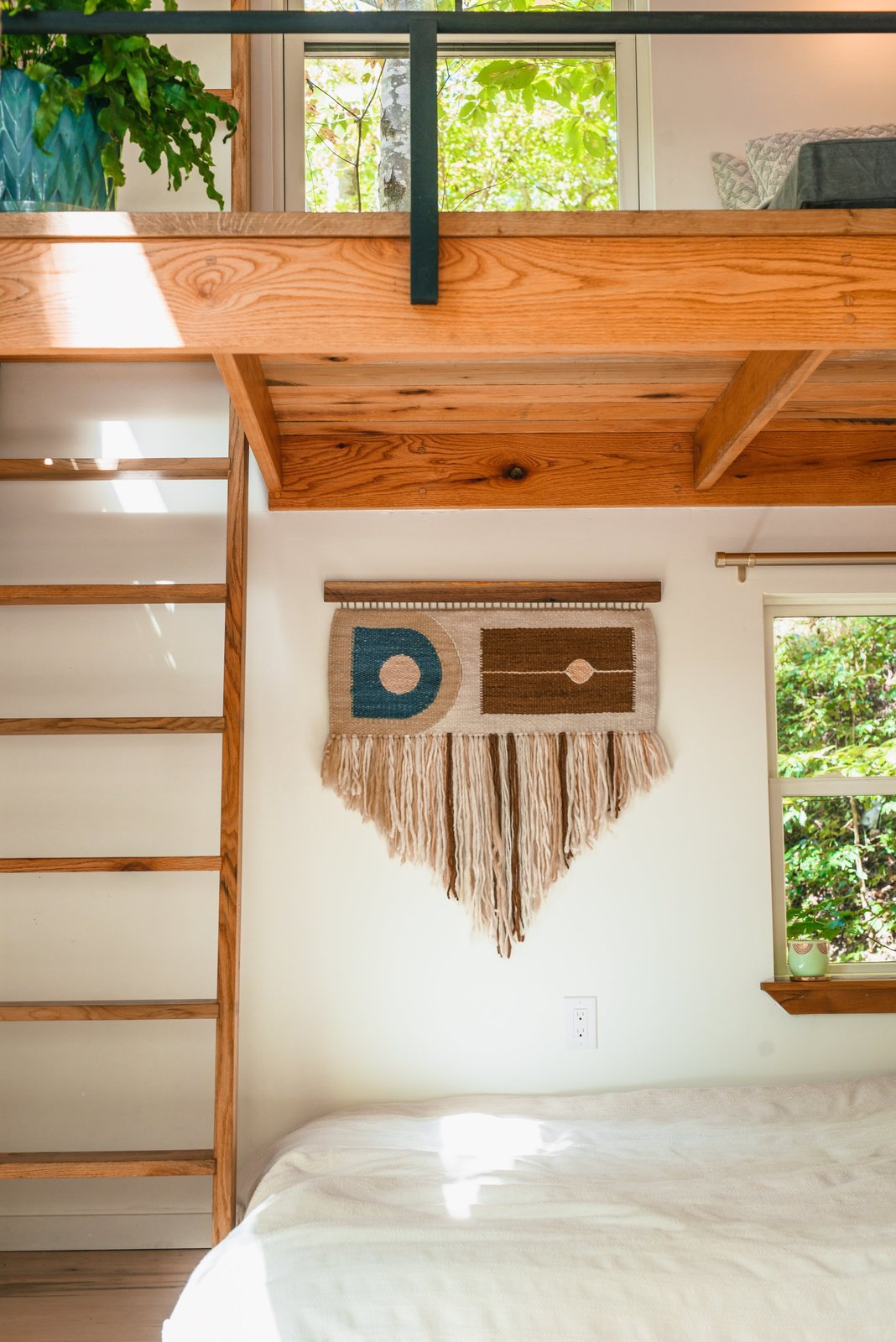"""Bedroom, Bed, and Medium Hardwood Floor The bedroom nook features a hand-loomed tapestry by Jessica Sanchez, owner of Rusted Earth, which produces sustainable, handcrafted home decor """"from the soil up"""".   Photo 8 of 11 in A Tiny Cabin in North Carolina Is an Enchanting Mix of Japanese and Scandinavian Style"""