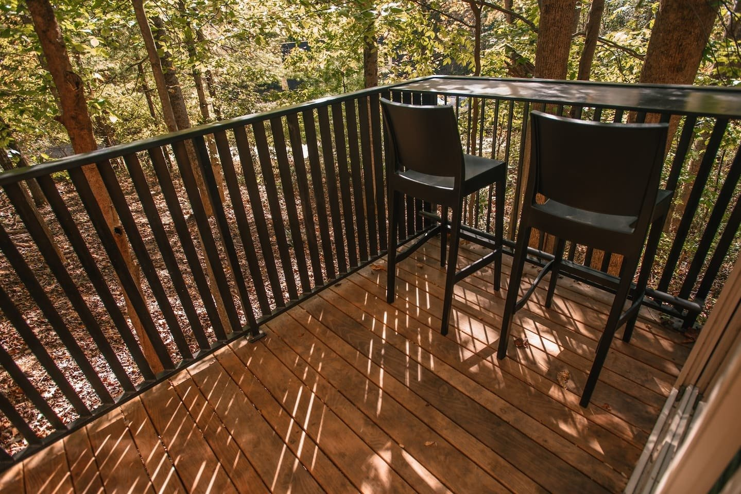 Outdoor, Wood Patio, Porch, Deck, and Small Patio, Porch, Deck The deck overlooking the surrounding forest is made of locally-milled black locust.   The custom iron railing was done by Iron Maiden Studios, a metalshop in Asheville.  Photo 11 of 11 in A Tiny Cabin in North Carolina Is an Enchanting Mix of Japanese and Scandinavian Style