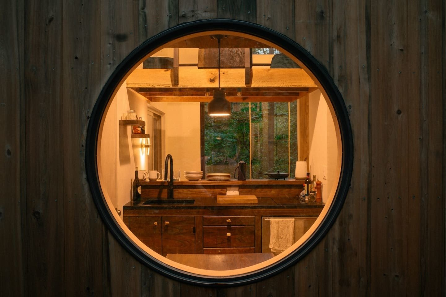 """Windows, Picture Window Type, and Wood Inspired by a homesteading commune he documented in Western North Carolina, photographer Mike Belleme built the Nook, a minimalist retreat in the woods that draws from both Japanese and Scandinavian design. He foraged much of the wood for the 400-square-foot cabin. """"Every kind of wood has a certain mood and personality,"""" he says. The exterior features an entranceway of oak blackened in the traditional Japanese method known as shou sugi ban.  Photo 2 of 11 in A Tiny Cabin in North Carolina Is an Enchanting Mix of Japanese and Scandinavian Style"""
