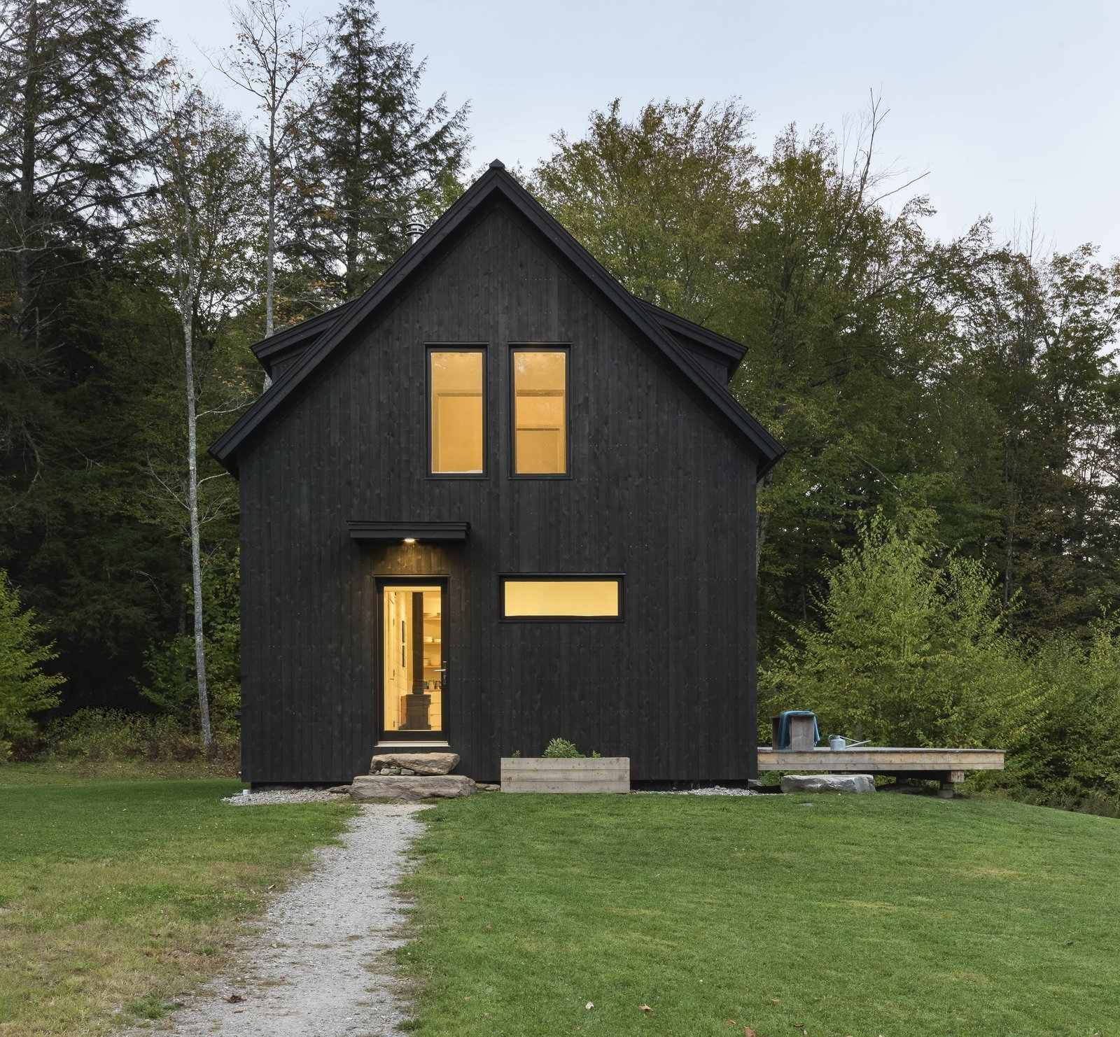 Outdoor, Raised Planters, Trees, Field, Large, Front Yard, Side Yard, Wood, Slope, Woodland, Shrubs, and Grass Close to Sugarbush's Mount Ellen and the Mad River Glen ski area, Fayston, Vermont, is the prime setting for Little Black House. Giving the retreat its name, Elizabeth Herrmann Architecture + Design only had 1,120 square feet to work with. Sitting just below the top of a hill, the black-stained cabin flaunts a classic gable structure with a stripped-down interior melding white walls and pale wood floors.  Outdoor Side Yard Raised Planters Photos from A Little Black Cabin Keeps Things Simple for a Family of Four in Vermont