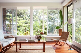 """Large windows allow the lush, tropical garden to become a focus of the interior design. Ginger replaced the previous bulky shades with a sleek, motorized, exterior shade system. """"They are on a timer,"""" she explains, """"so that they automatically lower in the late afternoon for about four hours."""""""