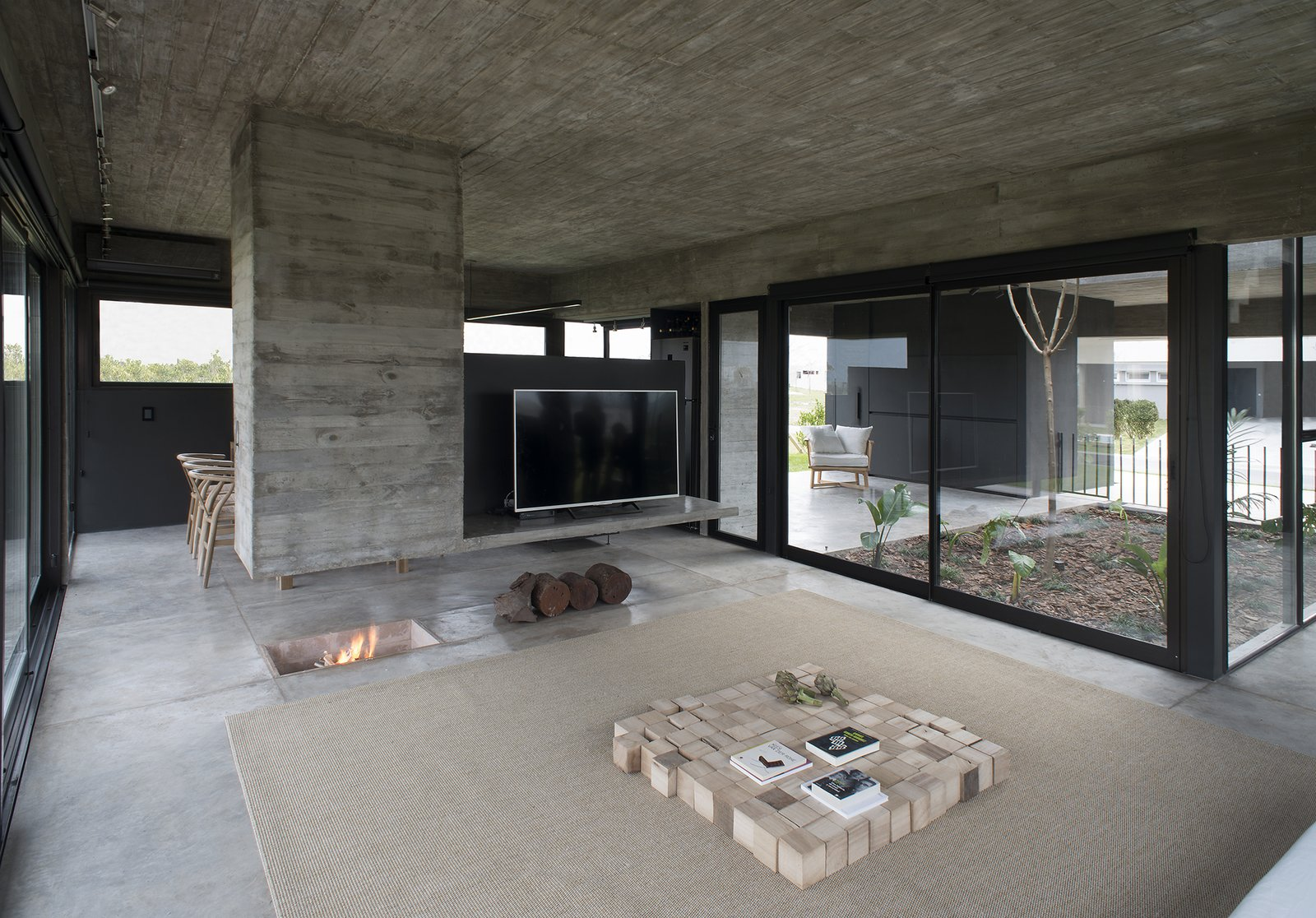 Living Room, Coffee Tables, Ceiling Lighting, Hanging Fireplace, Two-Sided Fireplace, Concrete Floor, Rug Floor, Carpet Floor, and Wood Burning Fireplace Castaños House by Arch. Ekaterina Kunzel & Arch. María Belén García Bottazzini  Castaños House