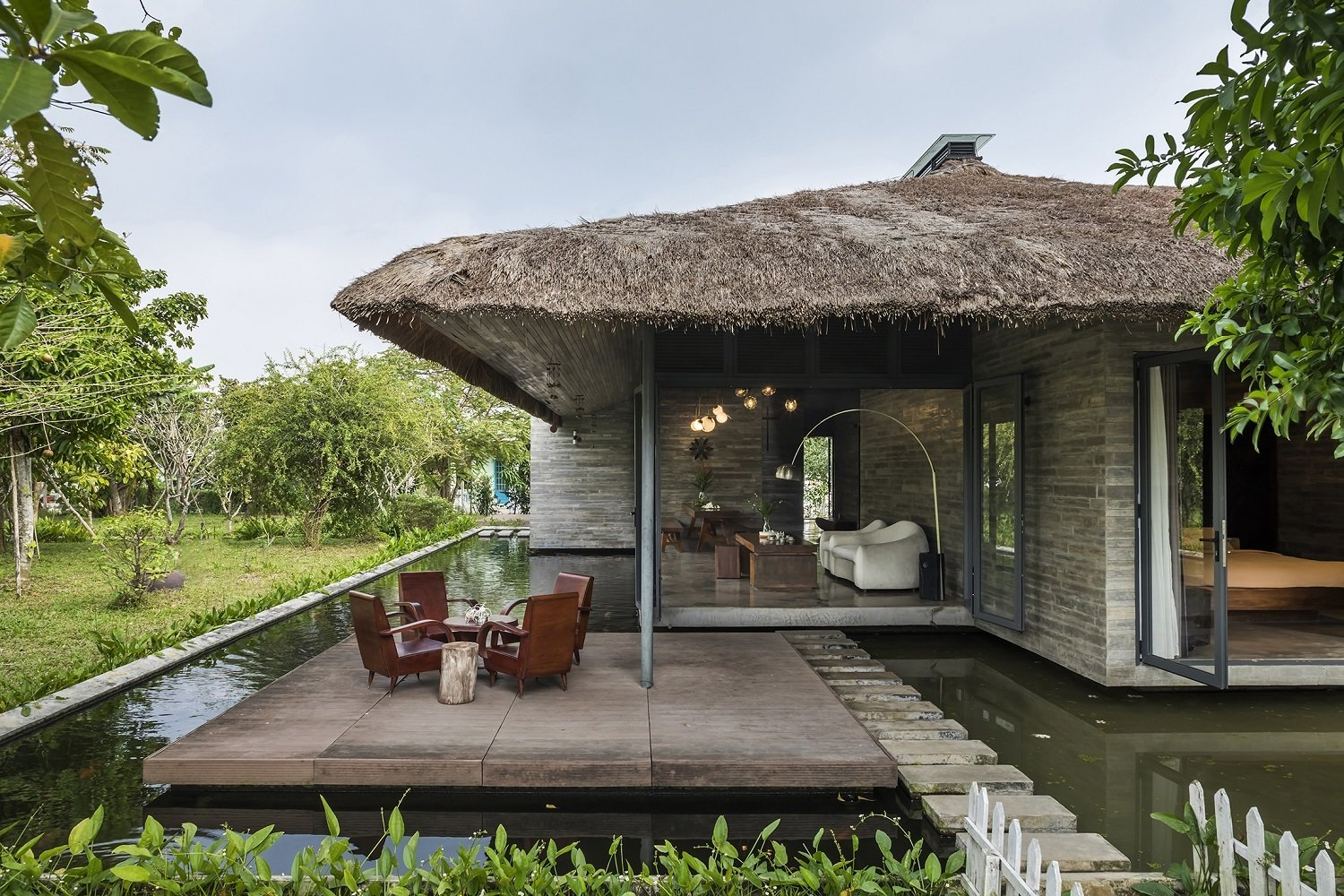Outdoor, Back Yard, Woodland, Grass, Garden, Front Yard, Trees, Small Pools, Tubs, Shower, and Gardens A koi moat surround this thatched-roof home—a collaboration between AmDesign Studio and Creative Architects—near Ho Chi Minh City.  Am house