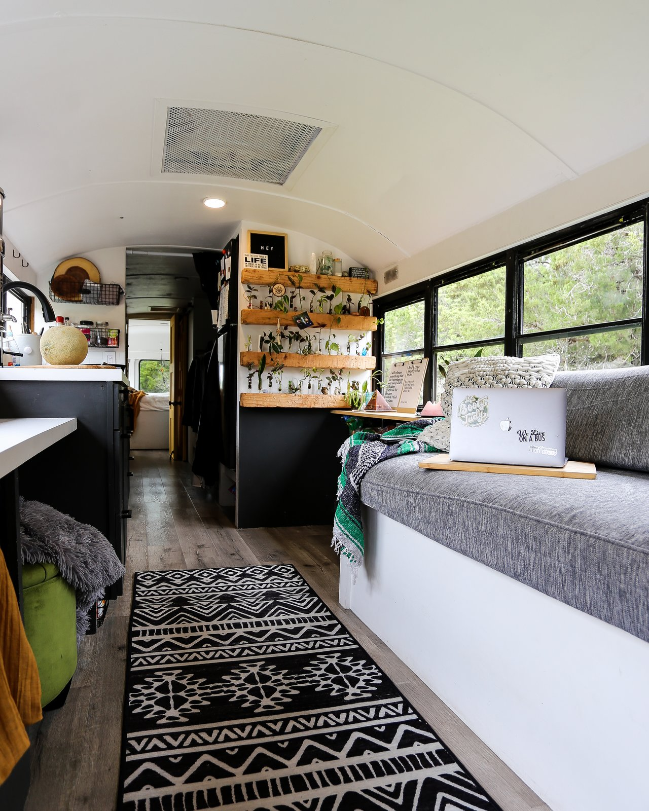 """Living Room, Storage, Ottomans, Sofa, Shelves, and Vinyl Floor The interior is 6'5"""".  We wanted a bus that was tall enough for my husband to stand in!  Big Booty Judy- Our Home on Wheels"""