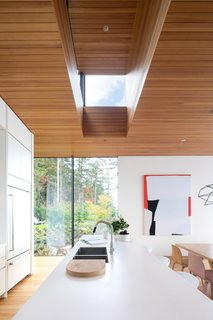 Roof lanterns illuminate the kitchen and dining area during the day. They are a low-maintenance alternative to skylights since they don't allow the forest's debris to accumulate and potentially block the natural light overhead.