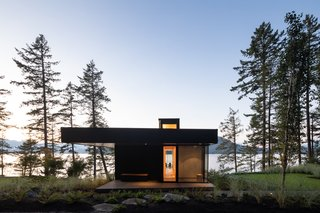Illuminated roof lanterns beckon to visitors, who must descend a forested roadway to approach Bowen Island House.