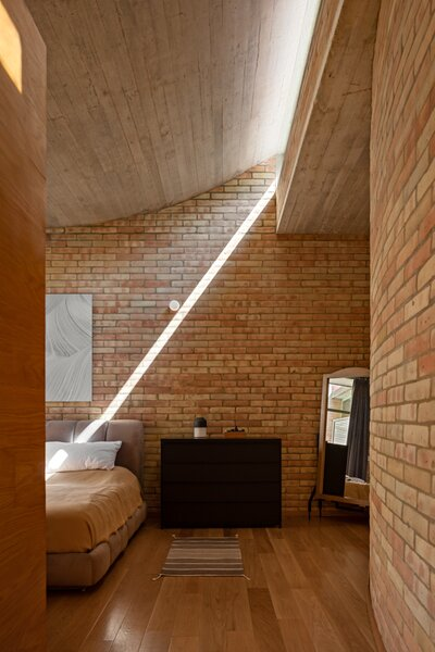 Afternoon sunshine casts a graphic beam on the wall of the master bedroom.
