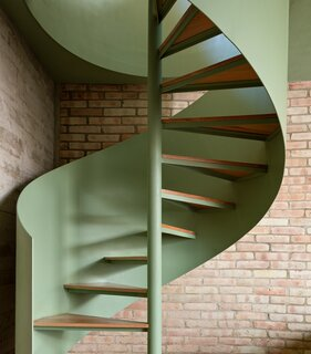 Curved forms reverberate throughout the property, including this spiral staircase that connects the two floors of the guesthouse.