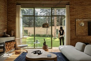 The Forest House's warm-toned living room looks out onto a verdant garden enclosure.