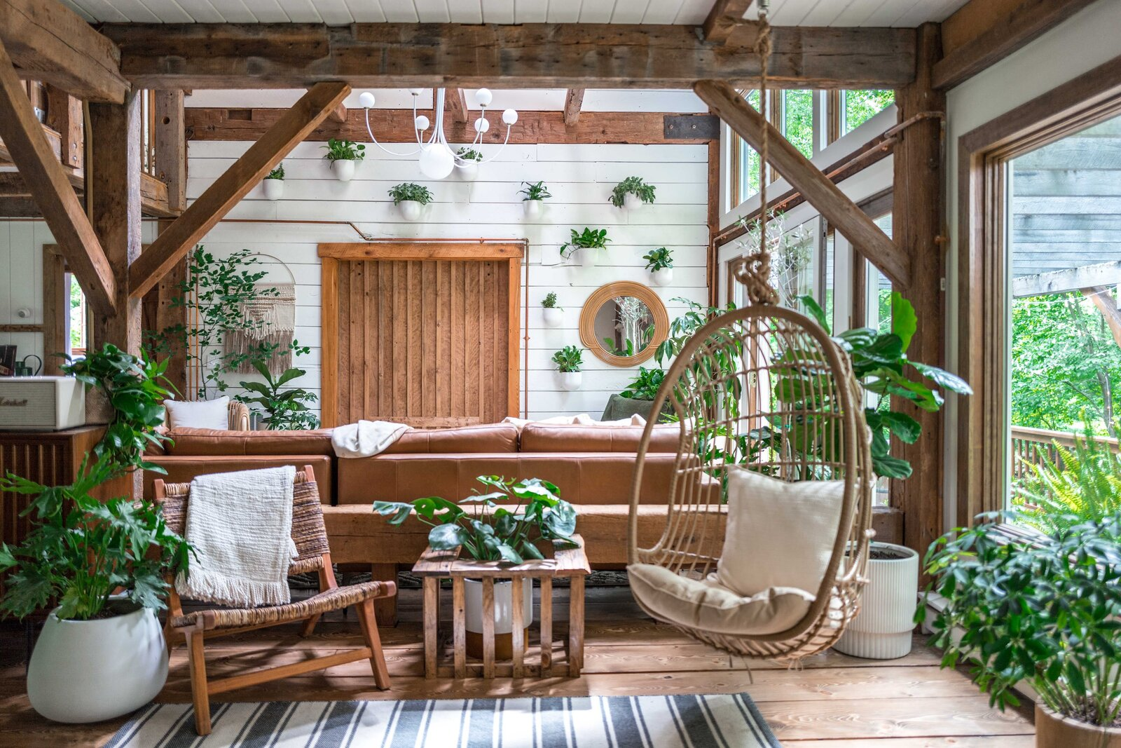 The Hunter Barnhouse by Danielle and Ely Franko living room with hanging chair and plant wall