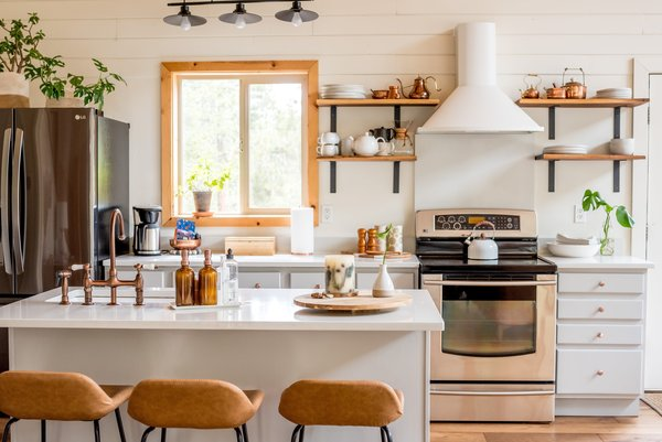 Open black walnut shelving replaced the upper kitchen cabinets, which now displays a vintage copper collection. The countertops are a crisp PentalQuartz in Carrara.