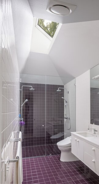 The maroon-tiled, walk-in shower has two showerheads and is well lit by a skylight from above.