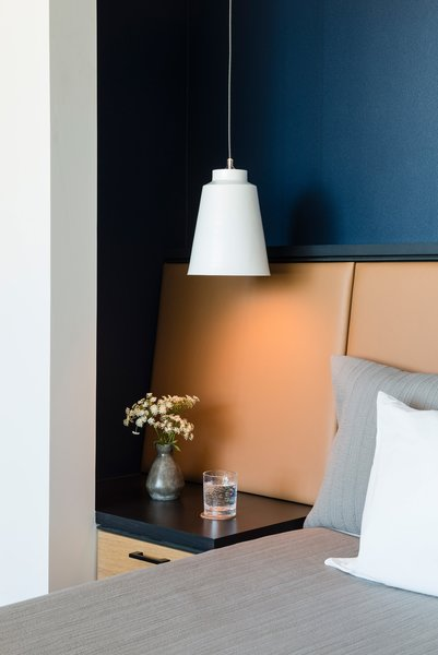 The leather headboard and bed in the guest room were custom designs, a collaboration between Flitch and Enabler. The side tables were sourced from ABC Carpet and Home; a Brendan Ravenhill Gran Barrel pendant light illuminates the space.