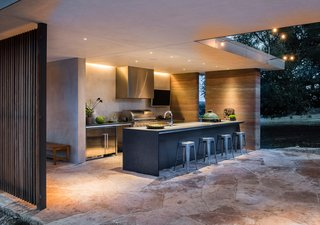 An outdoor kitchen is the perfect spot for entertaining poolside. Here, black granite countertops are paired with stainles- steel cabinets; in place of a cooking range, there's a a Wolf grill.
