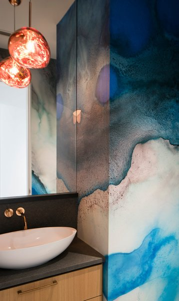 In the powder room, a Tom Dixon pendant dangles above a Ferguson Badeloft sink. Dreamy blue watercolor wallpaper from Black Crow Studios lines the walls.