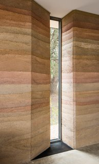 Slot windows in the thick rammed-earth walls allows natural light to stream in, while still keeping the home nice and cool.