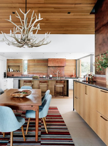 """Cabinetry was designed with the help of custom millwork company Flitch, and features another smart design trick: hiding a full pantry behind a standard cabinet door, keeping the painted millwork looking seamless. """"The details we love aren't necessarily the ones that show up in the photo,"""" says Jobe."""
