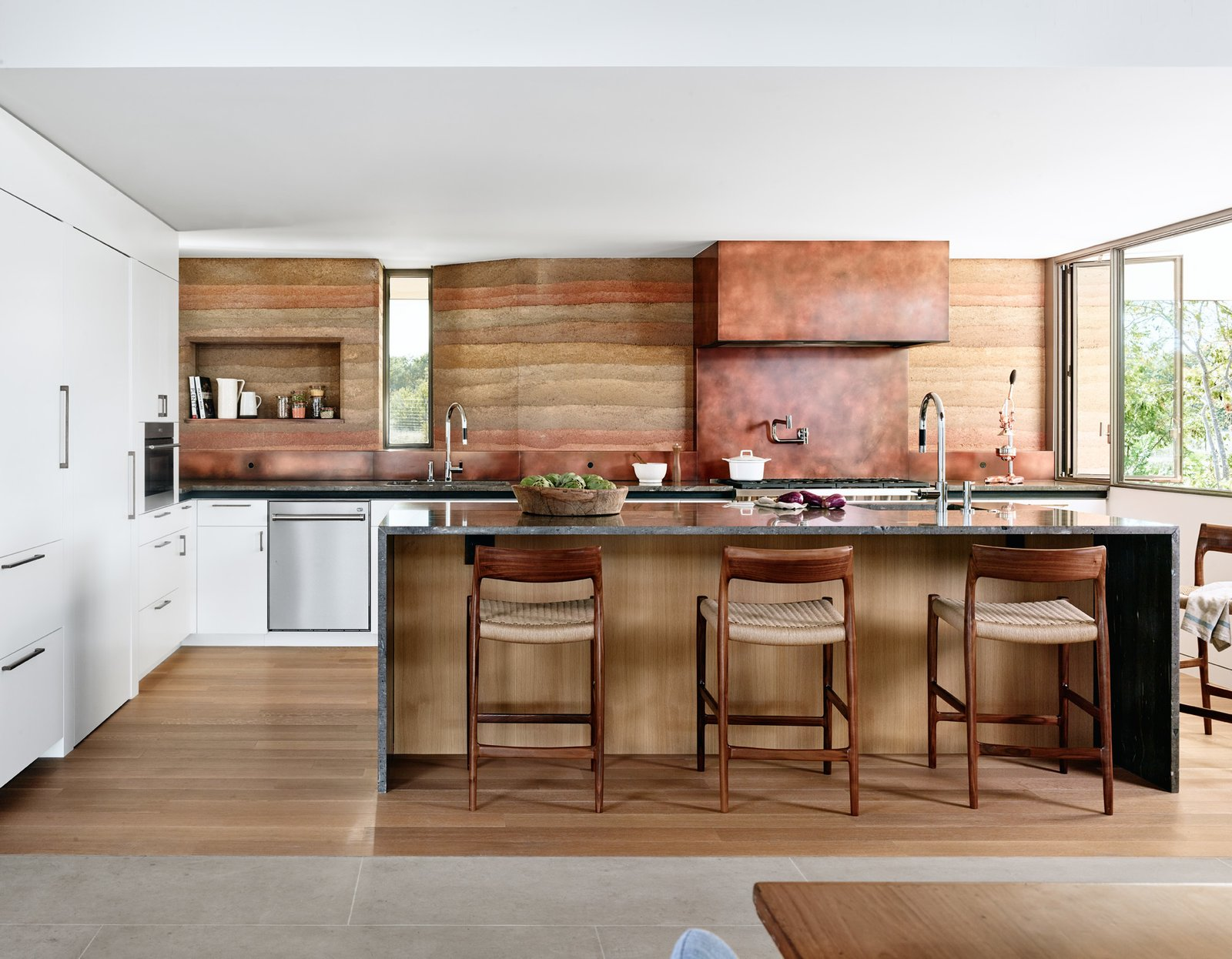 Jobe Corral Architects River Ranch house kitchen with rammed-earth wall and copper hood vent.