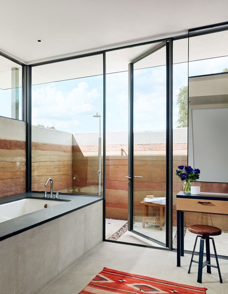 In the homeowners' ensuite, a Ferguson tub is surrounded by honed basaltina from Architectural Tile and Stone, while the flooring is limestone from Arcon. An inviting outdoor shower (surrounded by the rammed-earth walls and featuring plumbing fixtures by Signature Hardware) through the glass door offers an alternative opportunity for a spa-like experience under the Texas sky.