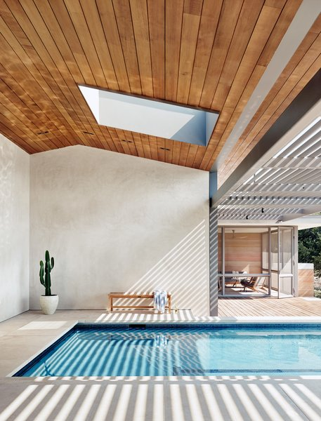 """The skylight above the pool is an odd shape, one Corral describes as a """"rectongulus."""" It's this spot, in a home full of beautiful moments, that she likes best. Above you is the sky. The rammed earth surrounds you, the view is in front of you, and the shadows of the trellis dance on the gentle waves of the turquoise pool. """"It's the place where you have all the connections,"""" says Corral."""