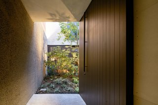 The light at the end of the tunnel-like entrance draws visitors to the oversized slab-style front door.