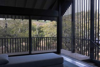 The meditation studio features a view of the property through black-stained slats.