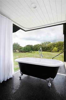 In the en suite, a black Victoria + Albert tub (with matching black American Universal penny tile) makes the perfect spot to soak up the view—though the shower curtains that line the windows can be drawn for a little more privacy. A shower head is mounted off to the right.