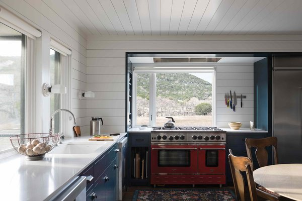 The windows over the sink open right onto the screen porch. A wall of built-in shelving offers both storage and a clever way to separate the kitchen and living room.