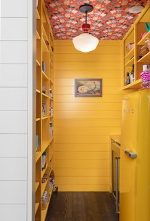 There are no upper cabinets in the kitchen, but a large walk-in pantry in the middle of the home—decked out in a cheery yellow paint and chicken-print wallpaper from Voutsa—provides ample storage.