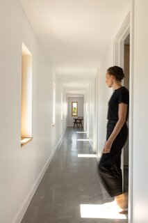 """In the bedroom hallway, a window is placed specifically in front of each door. """"It's like you have your own personal relationship with the window as you come through,"""" says Andrew Ashey, co-principal at AAmp Studio."""