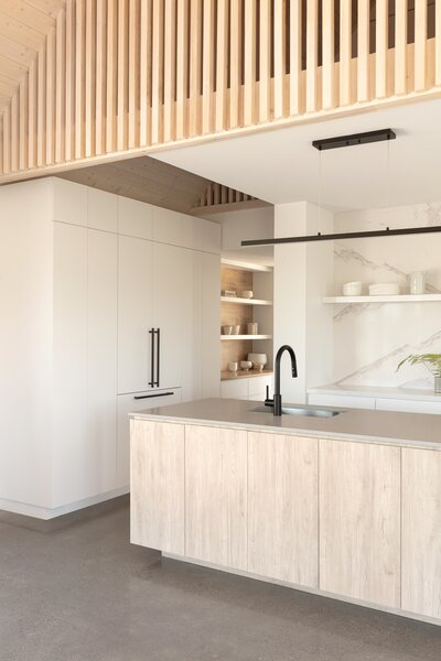 "In the kitchen, a concrete Caesarstone countertop echoes the flooring material; the slatted pine mezzanine is a nod to the ceiling finish. ""Everything is referencing something else,"" says Armstrong."