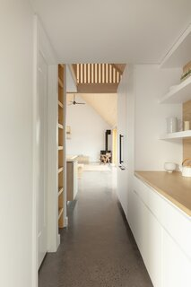 Appliances are hidden behind white panelling in the kitchen. A built-in nook in the kitchen entrance creates a niche to drop your things and disconnect from the road.