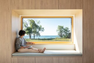 """The parents' bedroom is intentionally small, with a custom storage unit framing a giant window. """"It makes the views feel that much bigger,"""" says Handa."""