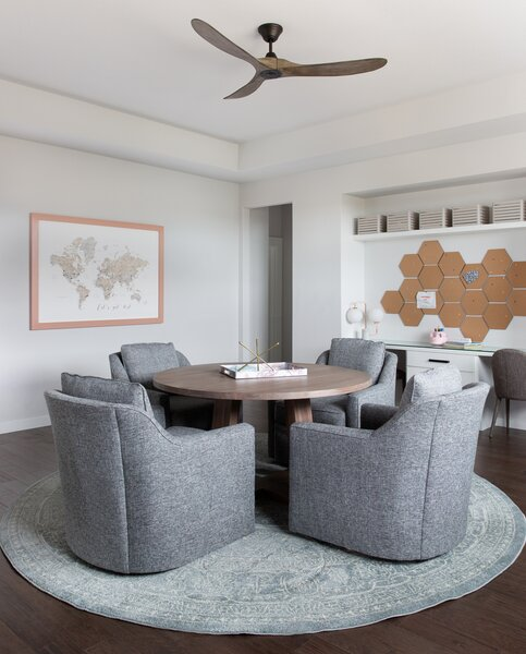 A desk along the wall is for computer work, but a communal round table in this home office by Bandd Design is a great place for kids to work on art projects or handwritten assignments in comfy chairs.