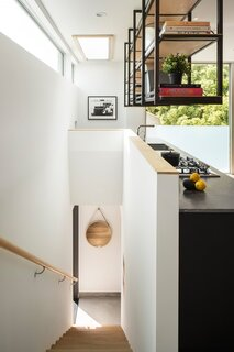 The honed marble countertop is a rich charcoal shade, with ultra-fine white veins. Simple black IKEA kitchen cabinets offer ample storage options for the tiny space.