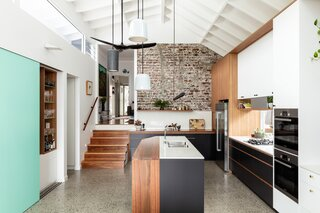 """There is no overhead lighting here, but that's just fine by Szczerbicki, who prefers to avoid """"blasting one massive level of light."""" Working closely with The Lighting Guild, he went for a more layered approach. Above the cabinetry, LED lights point up to illuminate the rafter, and a custom, linear pendant hangs above the island. """"Every piece of lighting was designed with a specific task in mind,"""" says Szczerbicki. """"As it gets darker, you slowly turn on key lights in key locations so the light level gradually grows."""""""