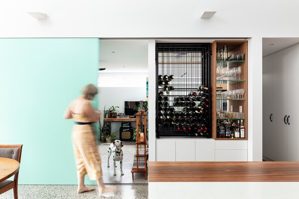 A sliding panel separates the living room and kitchen when necessary; the rest of the time, it conceals the wine and liquor cabinet.