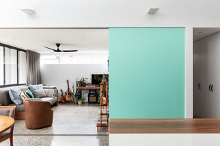 The sliding door between the kitchen and living room is painted a shade of sky blue that matches a hue favored by Italian bike brand Bianchi—a nod to Ben's previous passion for cycling. Chiseling the track into the concrete floor was no easy task, but builder Miso Building made it happen.
