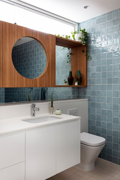 The newer downstairs bathroom features textured sky-blue tiles that nod to the natural ceramics Rose loves.