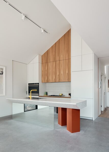 The kitchen island is made of poured terrazzo, balanced atop a mirrored slab and two orange posts for a playful, postmodern vibe.