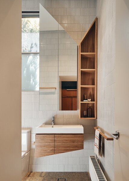 In the bathroom, a mottled Japanese tile from Academy Tiles brings texture and warmth. Plywood makes for an excellent material for shelving.