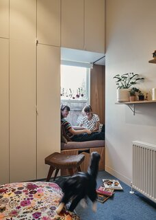"""A bunkette between the girls' bedrooms offers a private space for the close-knit sisters to share. """"They can crawl through, or sit and read, but if they have a fight they can close it,"""" says Dunin."""