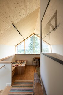 Although the home resembles a modernist barn, there are no beams within the structure. Rather, external timber trusses support the building.