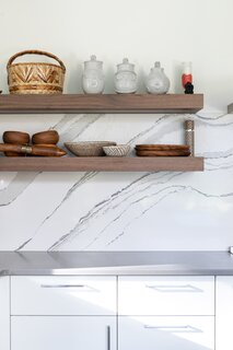 The kitchen backsplash is one solid piece of quartz, while the countertops are a blend of quartz and concrete. The floating shelves in the kitchen are all lit from underneath.