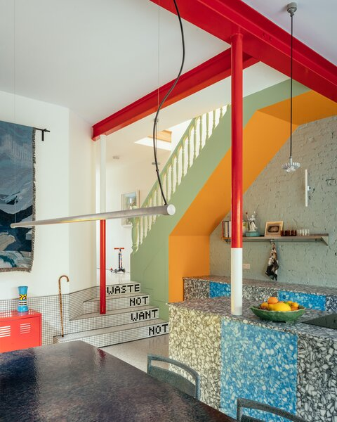 """Four steps take you down to the kitchen, tiled with Mat's grandmother's catchphrase, """"Waste not, want not."""" The countertops and storage are low, and finished in alternating colors, to add vertical emphasis in the long space."""