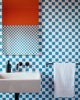Orange paint and blue-and-white checkerboard tiles are a gleeful match in the bathroom.